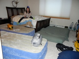 Nora surrounded by air mattresses and sleeping bags